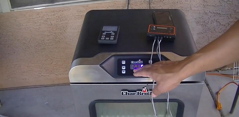 man controlling digital controls of CHAR-BROIL 19202101
