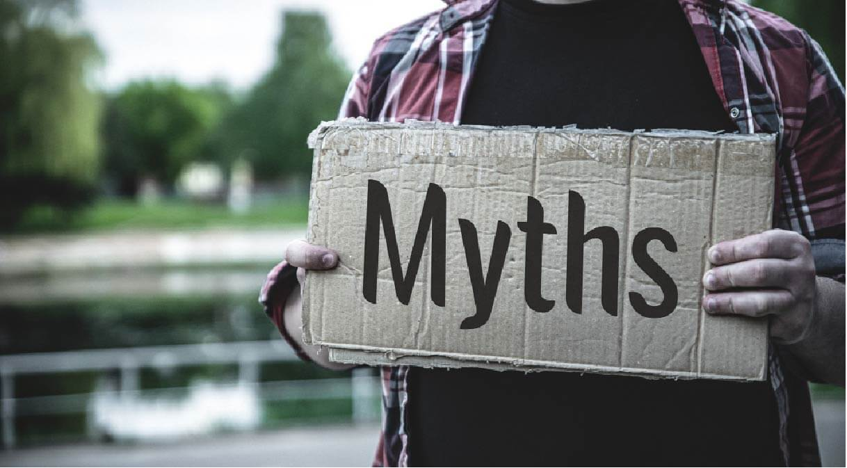 MAN HOLDING MYTHS CARDBOARD